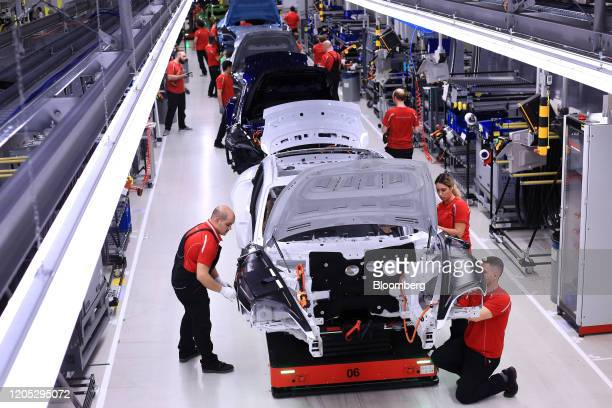 Employees work on the body shells of all-electric Porsche AG Taycan luxury automobiles on the production line inside the Porsche AG factory in...