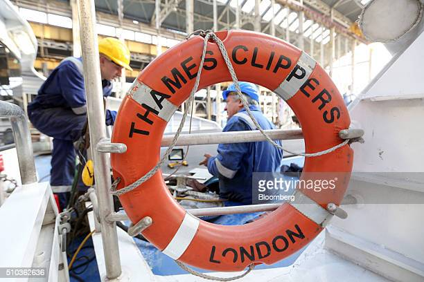 Employees work on the bow of a Thames Clipper catamaran at Turks boatyard in Chatham UK on Thursday Oct 29 2015 The Thames Clipper river bus service...