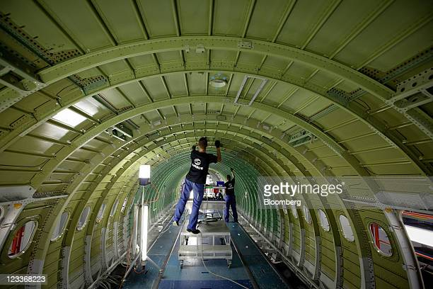 Employees work on the cabin section of an Airbus A320 aircraft at the Airbus SAS factory in Hamburg Germany on Thursday Sept 1 2011 AirAsia Bhd's...