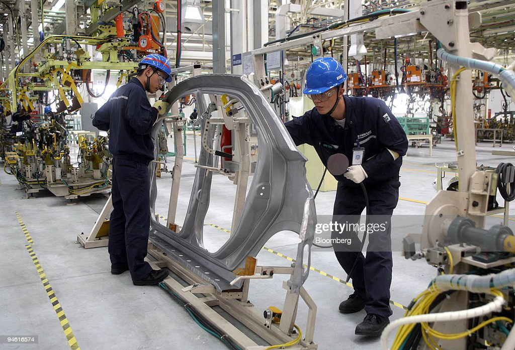 Employees work on the car frame of a Mazda2 sedan at Changan ...