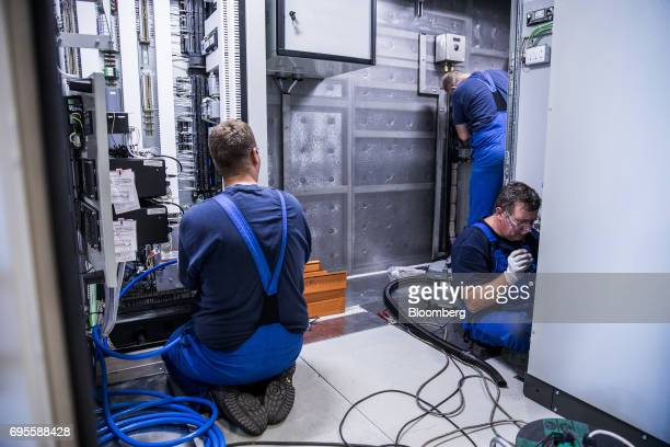 Employees work on the electrical wiring of a turbine inside the General Electric Co power plant in Veresegyhaz Hungary on Tuesday June 13 2017...