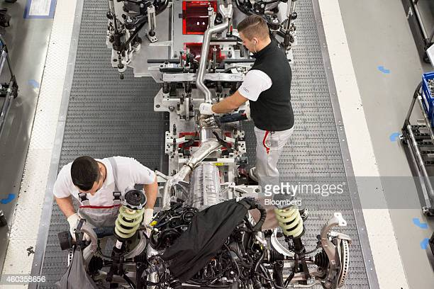 Employees work on the fiber glass reinforced plastic suspension springs on the chassis of an Audi RS automobile as it passes along Audi AG production...