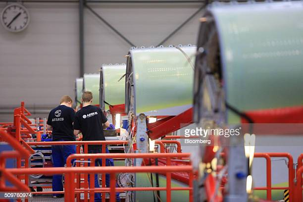 Employees work on the fuselage of Airbus A320 aircraft on the assembly line inside the Airbus Group SE factory in Hamburg Germany on Friday Feb 12...