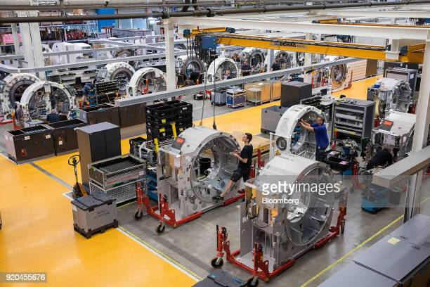 Employees work on the gantries of a Siemens Somatom computerized tomography scanner machines while on the assembly line at the Siemens AG...