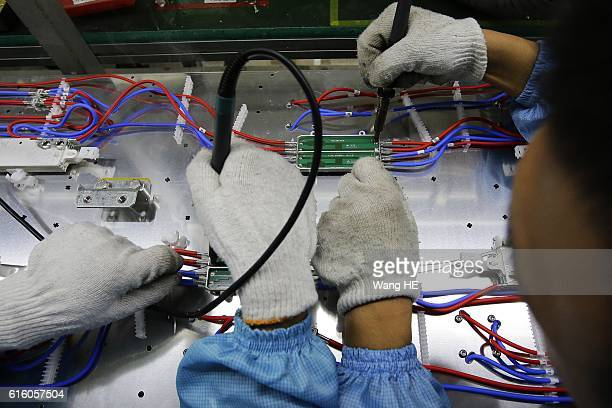 Employees work on the production line at Hongxin Communication Technology Company on October 21 2016 in Wuhan Hubei province China Hongxin...