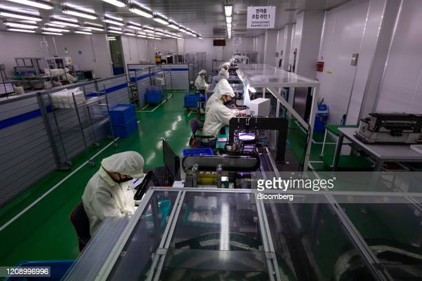 Employees work on the production line of the Ichroma Covid19 Ab testing kit at the Boditech Med Inc headquarters in Chuncheon South Korea on Friday...