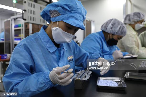 Employees work on the production line of the Ichroma Covid19 Ab testing kit used in diagnosing the coronavirus at the Boditech Med Inc headquarters...