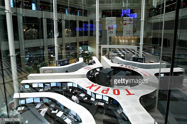 Employees work on the trading floor of the Tokyo Stock Exchange in Tokyo Japan on Thursday Oct 17 2013 Japanese shares rose with the Topix index...