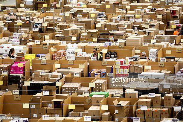 Employees work on the warehouse floor at an Amazoncom Inc fulfillment center in Peterborough UK on Tuesday Nov 15 2016 The online retail giant needs...