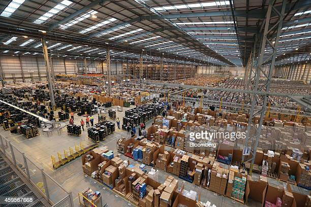 Employees work on the warehouse floor at one of Amazoncom Inc's fulfillment centers in Peterborough UK on Tuesday Nov 25 2014 Online spending will...