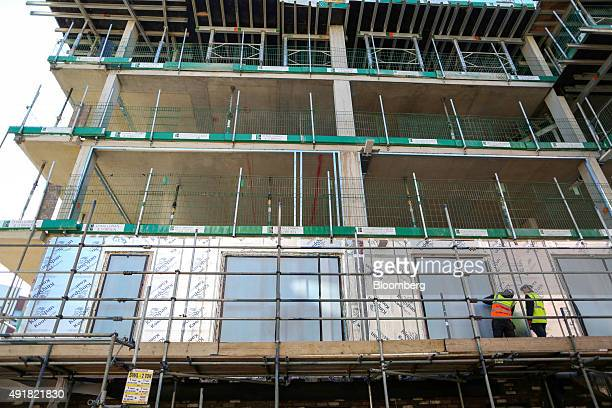 Employees work on the window frame of an apartment block at a Countryside Properties Plc brownfield regeneration residential construction site in...