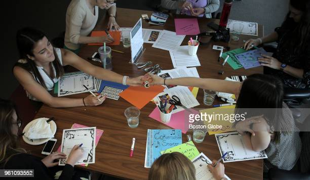 JLL employees work on their music booklets as part of a letter exchange program with the Boston Children's Chorus in Boston on May 3 2018 For a race...
