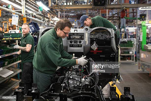 Employees work on wiring connected to the dashboard of a Land Rover Defender automobile at Tata Motors Ltd's Jaguar Land Rover vehicle manufacturing...