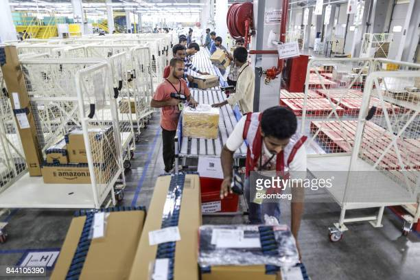 Employees work to prepare packages for shipment on the conveyor belt at the Amazoncom Inc fulfillment center in Hyderabad India on Thursday Sept 7...