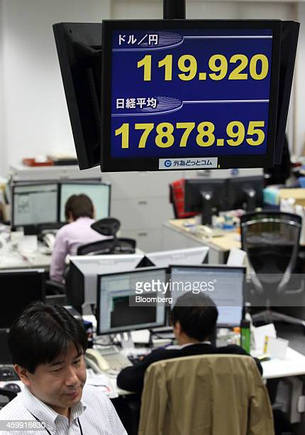 Employees work under a monitor displaying the exchange rate of the yen against the US dollar top and the Nikkei 225 Stock Average figure at a foreign...