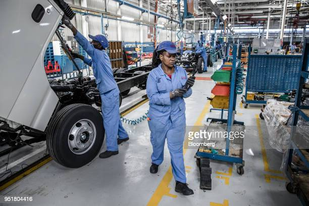 Employees work under the cabin of an Isuzu NPR NSeries Truck on the assembly line inside the Isuzu East Africa Ltd plant in Nairobi Kenya on Thursday...