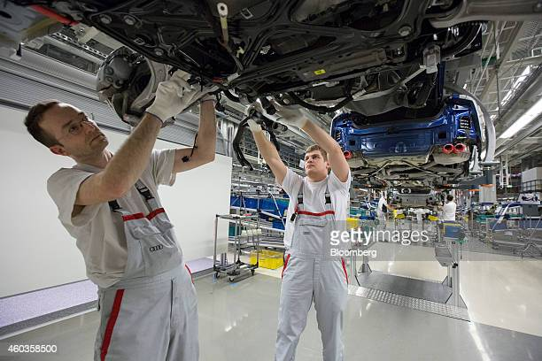 Employees work underneath an automobile chassis on the Audi A6 and A7 production line inside the Audi AG factory in Neckarsulm Germany on Wednesday...