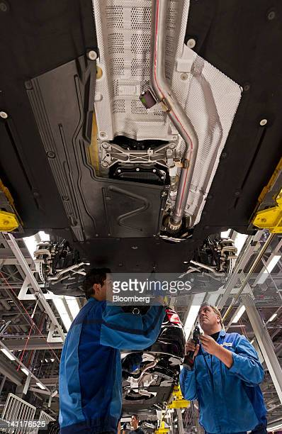 Employees work underneath Bayerische Motoren Werke AG 3series automobiles as they travel along the production line at the company's assembly plant in...