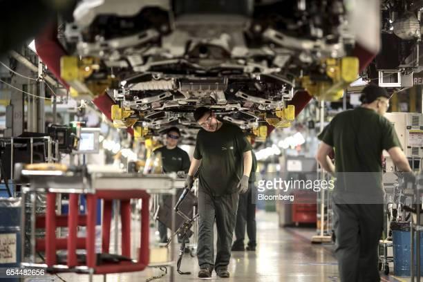 Employees work underneath Jaguar automobiles on the final assembly line at Tata Motors Ltd.'s Jaguar assembly plant in Castle Bromwich, U.K., on...