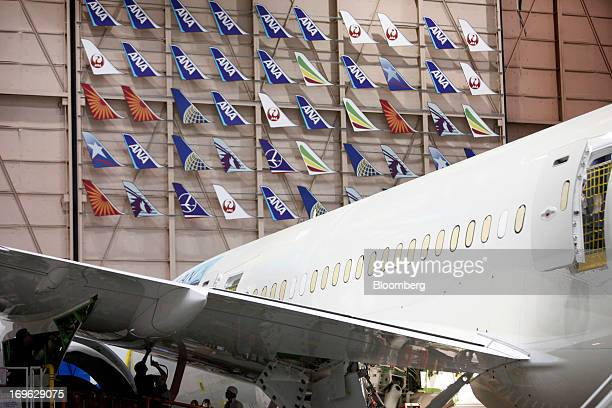 Employees work underneath the wing of a Boeing Co 787 Dreamliner during final assembly of the airplane at the Boeing Co factory in Everett Washington...