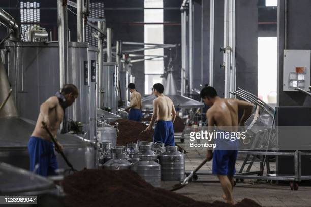Employees work with piles of sorghum in the fermentation and distillation workshop at Chongqing Jiangxiaobai Liquor Co.'s Jiangji Distillery in...
