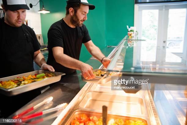"""funcionários que trabalham em zero resíduos de mercearia orientada e tirar a loja de alimentos. - """"martine doucet"""" or martinedoucet - fotografias e filmes do acervo"""