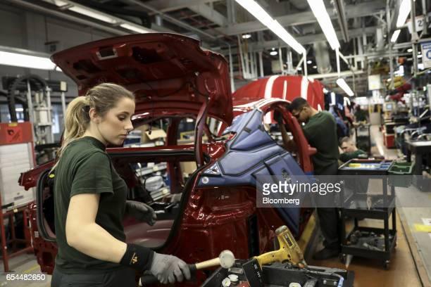 Employees works on a Jaguar automobile on the production line at Tata Motors Ltd.'s Jaguar assembly plant in Castle Bromwich, U.K., on Thursday,...