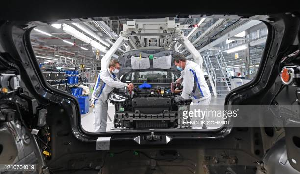 EmployeesMax Bruehmann and Heiko Gruner wear face masks as they work on the assembling of a Volkswagen ID.3 electric car at the plant of German car...