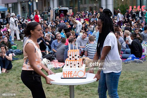 Employes Christina Anderson and Amanda ClarkeTaitt carried a cake for TIFF's 40th birthday party that was celebrated at David Pecaut Square A...