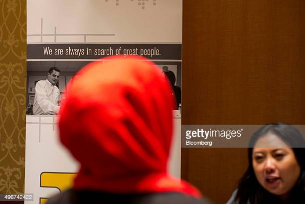 Employment signage hangs as a job seeker left speaks with a recruiter during the San Jose Career Fair in San Jose California US on Tuesday Nov 10...