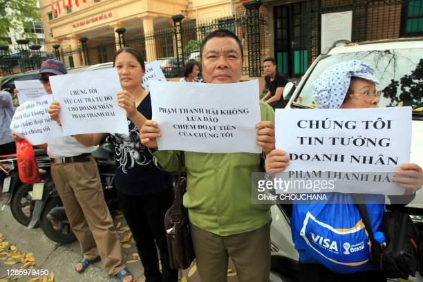 Employés et gens du villaged'un homne d'affaires vietnamien ayant été condamné pour fraude fiscale protestent contre sa condamnation en manifestant...