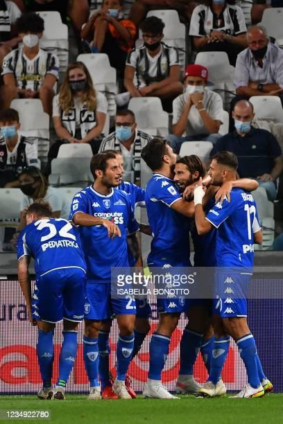 Empoli's Italian midfielder Leonardo Mancuso celebrates with teammates after he scored the first goal during the Italian Serie A football match...