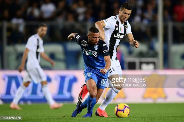 Empoli's midfielder Ismael Bennacer from Algeria fights for the ball with Juventus' Portuguese forward Cristiano Ronaldo during the Italian Serie A...