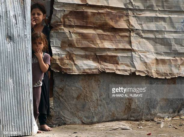 TOPSHOT Empoverished Iraqi children stand by their home's entrance in Baghdad's mostly Shiite Sadr City district on October 12 2018
