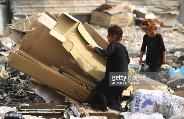 Empoverished Iraqi girls collect cardboard from waste for sale in Baghdad's mostly Shiite Sadr City district on October 12 2018