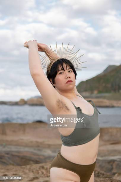 empowered woman showing armpit hair in bikini - armpit hair woman stock pictures, royalty-free photos & images