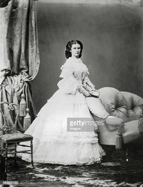 Empress Elisabeth from Austria Whole figure standing half right white dress opened book in her hands Photograph by Ludwig Angerer later fall 1860...