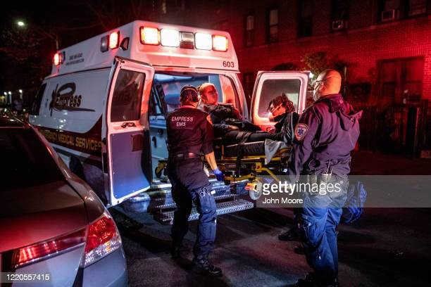 Empress EMS Capt AJ Briones R looks upon an emergency scene as medics load a patient into an ambulance on April 22 2020 in Yonkers New York Even as...