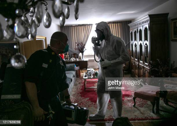 Empress EMS Captain AJ Briones passes a Yonkers fireman wearing personal protective equipment at an apartment on April 06 2020 in Yonkers New York...
