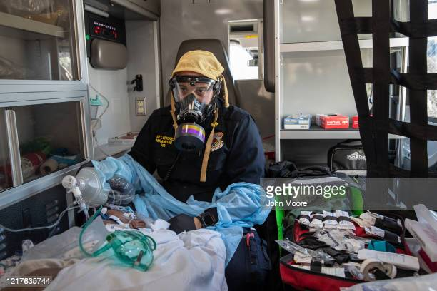 Empress EMS Captain AJ Briones wearing a personal protective equipment respirator cares for a suspected COVID19 patient while in route by ambulance...