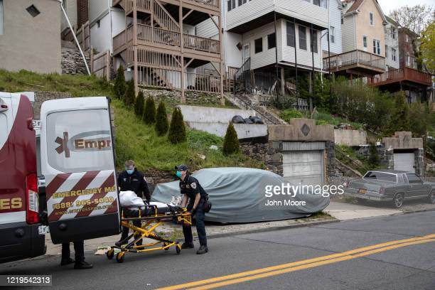 Empress EMS Paramedic Rich Straub , lifts a patient with COVID-19 symptoms into an ambulance on April 17, 2020 in Yonkers, New York. Yonkers, located...