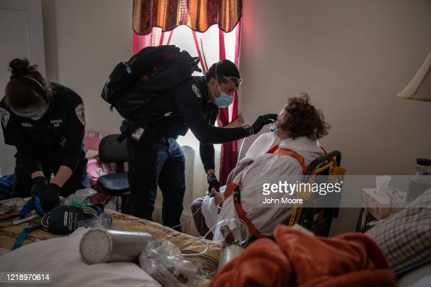 Empress EMT Rick Grohs and fellow EMS medics assist a patient with COVID-19 symptoms before transporting her to the hospital on April 14, 2020 in...