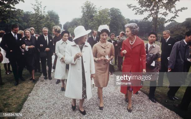 Empress Kojun of Japan chats with Queen Ingrid of Denmark in the garden of the Danish royal country home; In the center is Mrs. Ogawa, wife of the...