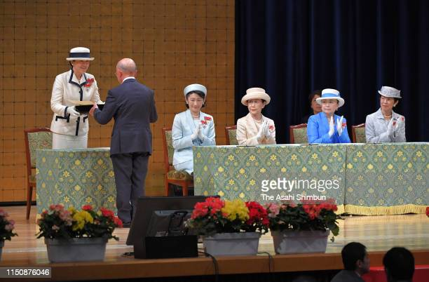 Empress Masako presents a certificate while Crown Princess Kiko of Akishino, Princess Hanako of Hitachi, Princess Nobuko of Mikasa and Princess...