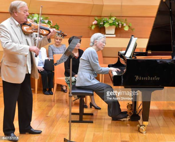 Empress Michiko plays piano with violinist Werner Hink during a workshop of the Kusatsu International Summer Music Academy Festival at Kusatsu...
