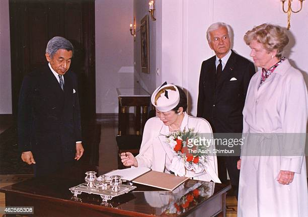 Empress Michiko sign on the guest book while Emperor Akihito Germany President Richard von Weizsacker and his wife Marianne watch after the welcome...