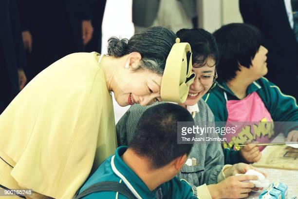 Empress Michiko talks to children during her visit to the Miyagi Prefecture Rifu School For Handicapped Children on October 6 1992 in Rifu Miyagi...
