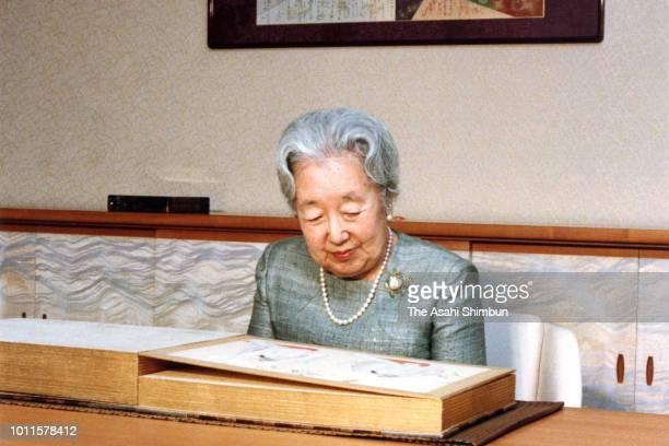 Empress Nagako watches an art book during a photo session ahead of her 82nd birthday at the Imperial Palace on February 1, 1985 in Tokyo, Japan.