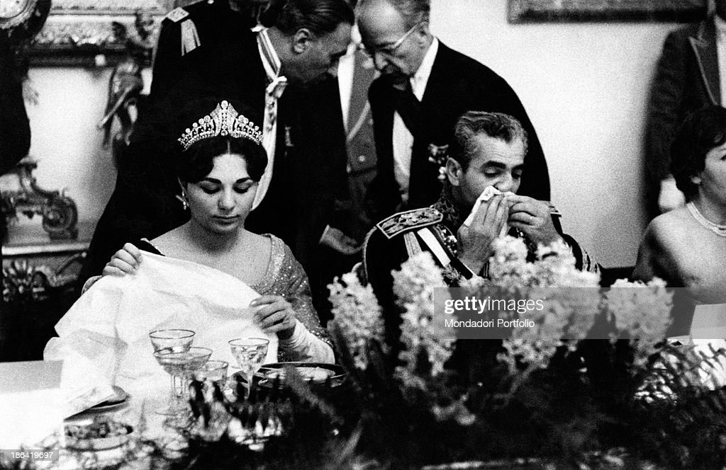 Farah Pahlavi and Mohammad Reza Pahlavi sitting at the table : News Photo