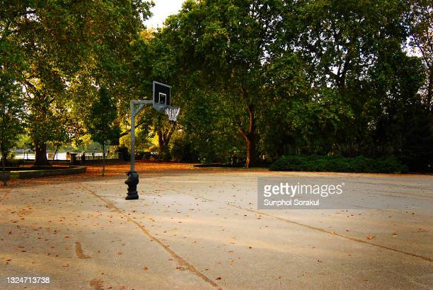 a empth basketball court inside bishop's park during autumn, fulham, london uk - basketball sport stock pictures, royalty-free photos & images